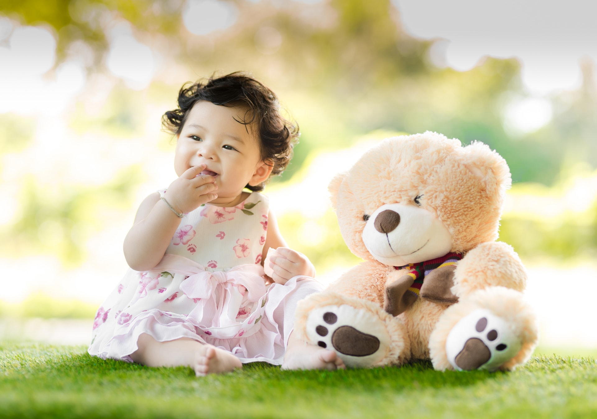 baby-sitting-on-green-grass-beside-bear-plush-toy-at-daytime-1166473