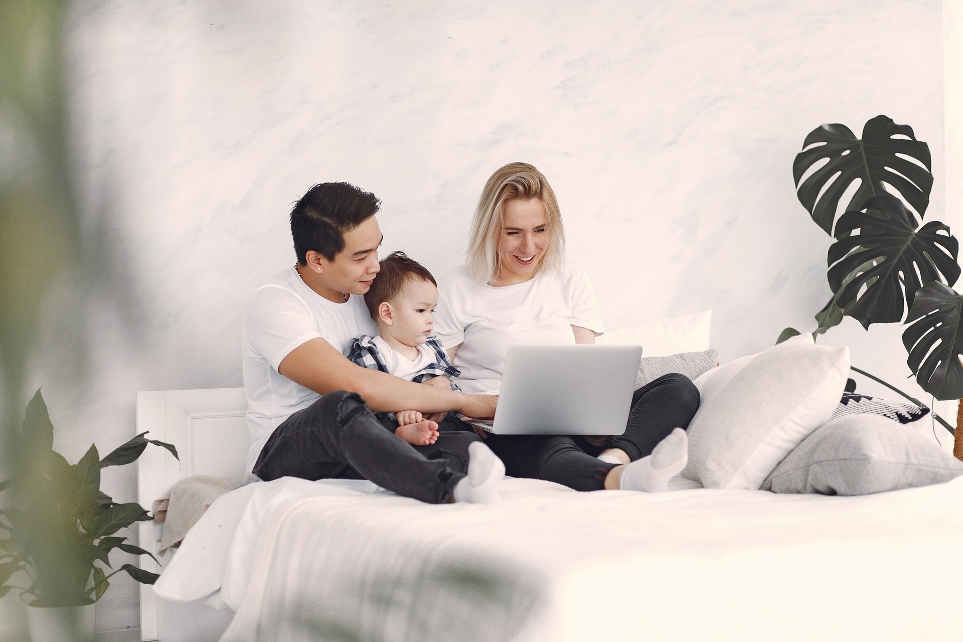 man-and-woman-sitting-on-white-bed-using-laptop-computer-3912387